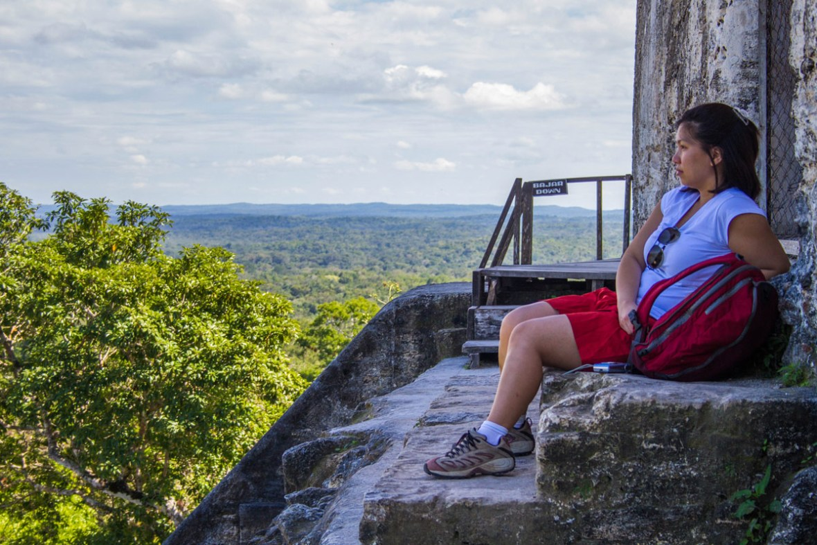 A woman wearing red shorts and sunglasses sits with a backpack and takes in the view from the top of a tall Mayan pyramid
