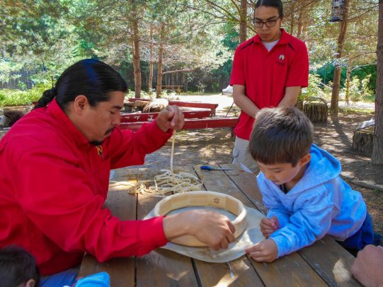 Elder teaches young boy how to make a drum as part of the Great Spirit Circle Trail Voice of the Drum Make and Take experience on Manitoulin Island.