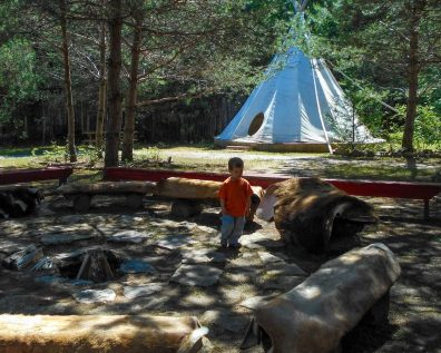 Young boy exploring the area around the firepit at the Great Spirit Circle Trail on Manitoulin Island.