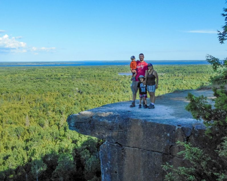 Family picture on the famous lookout at the Cup and Sauce Trail which is one of the Great Spirit Circle Trail Experiences on Manitoulin Island.