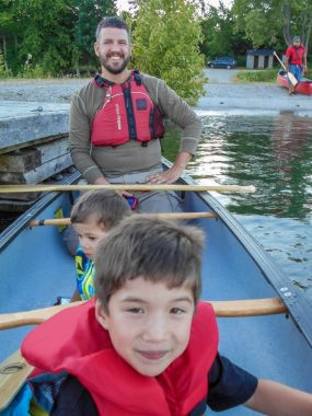 Father and sons on a family canoe ride on the Great Spirit Circle Trail Sunset Canoe Ride Experience on Manitoulin Island.