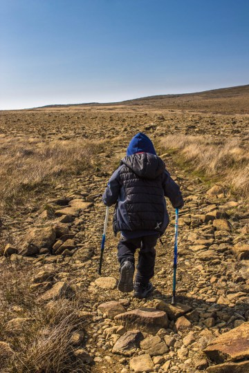 A young boy holding hiking poles treks along a rocky terrain in Gros Morne National Park - Hiking Green Gardens in Gros Morne National Park