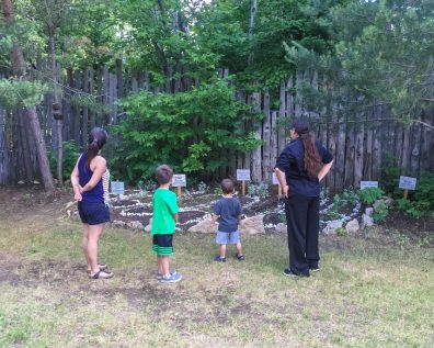 Women and two children looking onto a garden with herbs and other plants at the Great Spirit Circle Trail glamping site on Manitoulin Island.
