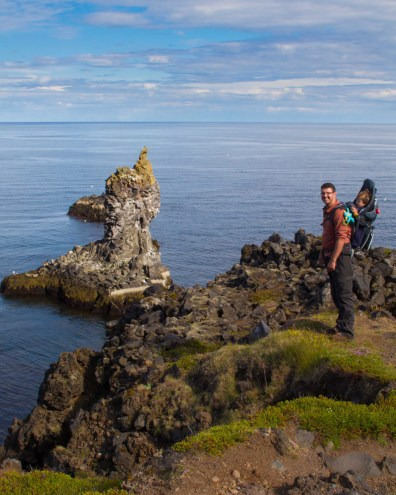 A father with a son in a backpack carrier look out over cliffs and volcanic stacks on the coast of Iceland - An Epic 14 Day Iceland Itinerary