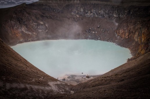 A group of people hike down to a volcanic crater with milky white water - An Epic 14 Day Iceland Itinerary