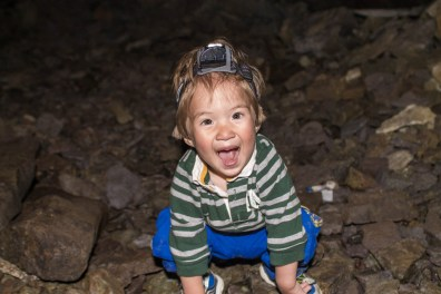 A young boy wearing a headlamp smiles excitedly inside a cave - An Epic 14 Day Iceland Itinerary