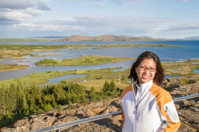A woman smiles while standing at an overlook. Behind her are grasslands and lakes - Epic 14 Day Iceland Itinerary