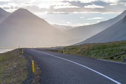 A mist lightly covers a highway running through mountains - An Epic 14 Day Iceland Itinerary