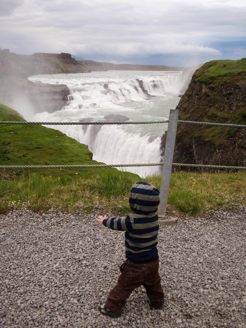 A young boy wearing a hoodie watches a large waterfall cascade into a canyon - An Epic 14 Day Iceland Itinerary