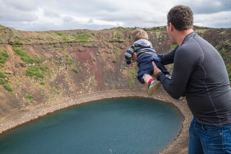 A father pretends to throw a laughing young boy into a volcanic crater - An Epic 14 Day Iceland Itinerary