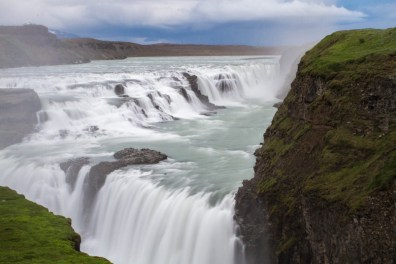 A double waterfall falls into a canyon on the Golden Circle in Iceland. - Epic 14 Day Iceland Itinerary