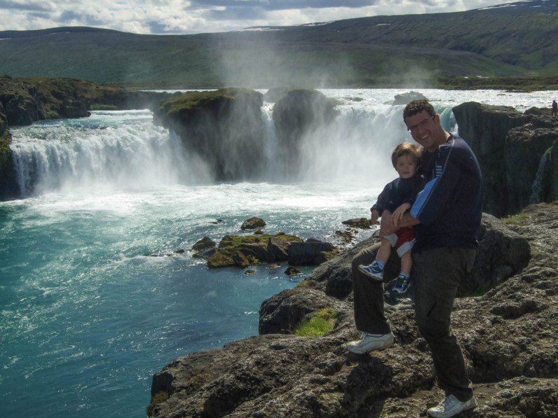 A father and son smile at the edge of a large waterfall - An Epic 14 Day Iceland Itinerary