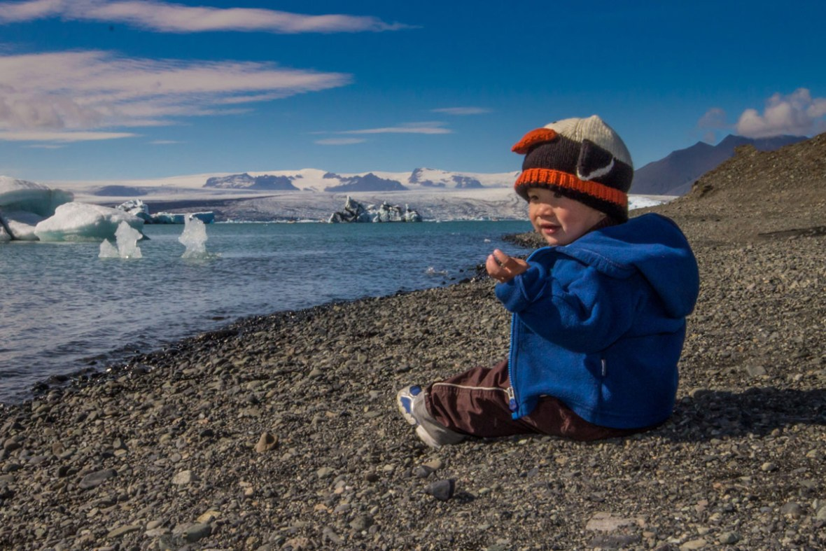 A young boy wearing a penguin cap looks at glaciers from a rocky beach - An Epic 14 Day Iceland Itinerary