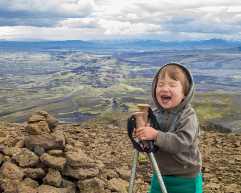 A young boy holding hiking poles laughs on a mountain top - An Epic 14 Day Iceland Itinerary