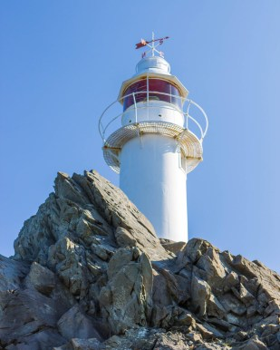 A white lighthouse with red accents posed on top of a rocky cliff - Newfoundland Viking Trail