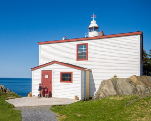 Two young boys knock on the door of a lighthouse - Newfoundland Viking Trail