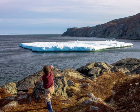 A young boy points off a rocky coast towards a large iceberg - Newfoundland Viking Trail