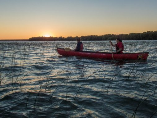 Two people on a canoe witness a gorgeous sunset on Lake Manitou as part of the Great Spirit Circle Trail Sunset Canoe Experience on Manitoulin Island.