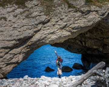 A young boy standing under a rock arch by the ocean points to the sky with a toy sword - Newfoundland Viking Trail