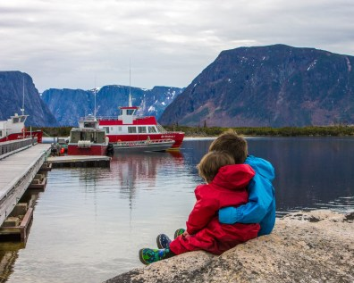 Two young boys wearing rain outfits hug each other while looking out over boats - Newfoundland Viking Trail
