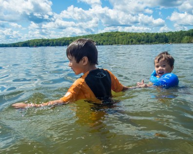 an older brother helping a younger brother swim at the beach - Top things to do in Bon Echo Provincial Park