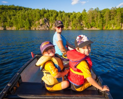 A mother and two sons smile from the front of a canoe with a forest in the background - Top things to do in Bon Echo Provincial Park