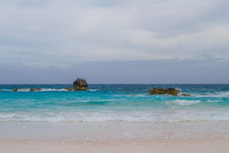 View of pink sands with waves crashing in Horseshoe bay is known as the best Bermuda beach.
