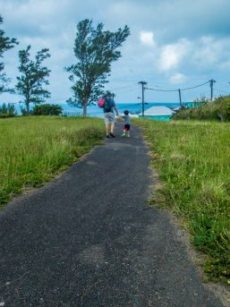 Father and son walk on path to the beach in St. George's Parish.
