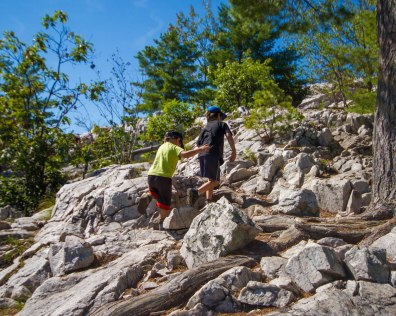 Two young boys climb over boulders on a hike - Hiking the Crack in Killarney with Kids