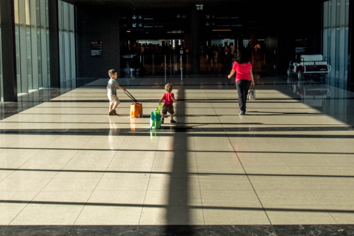 A mother and two young boys walk through an airport walkway - plan international family vacations