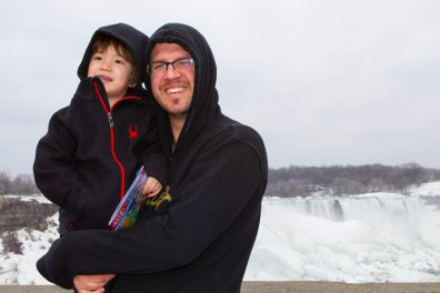 A man and his young son pose in front of Niagara Falls during the winter