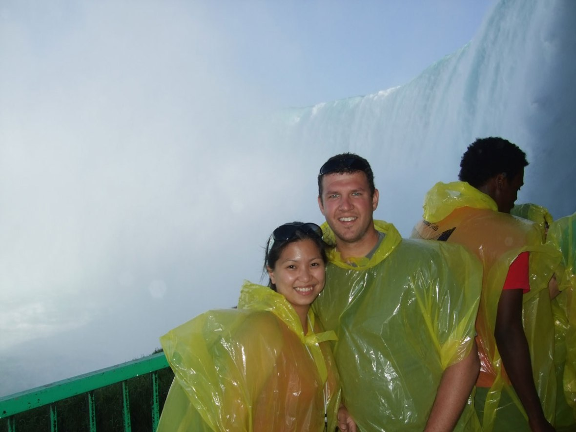 A young couple stands next to Niagara Falls wearing yellow rain ponchos
