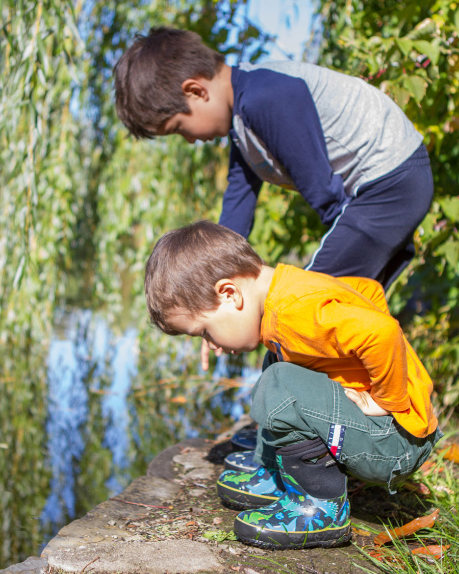 Two young boys check out a pond while wearing their bog boots - Bogs kids winter snow boots