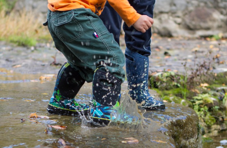 Closeup of the feet of two young boys splashing in a stream - Bogs kids winter snow boots