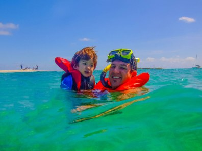 A father and young son wearing lifejackets float in blue Caribbean waters - Swimming with turtles in the Tobago Cays