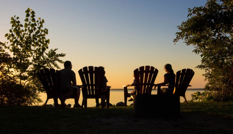 Family on muskoka chairs watch the sunset over Thousand Islands National Park.