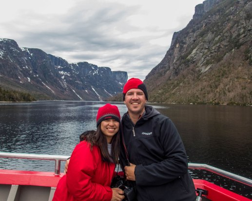 A mixed race couple wearing toques smile a the camera while touring Western Brook Pond in Gros Morne National Park