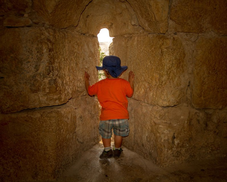 A young boy in a tilley hat stares out a narrow slot in a castle in Jordan