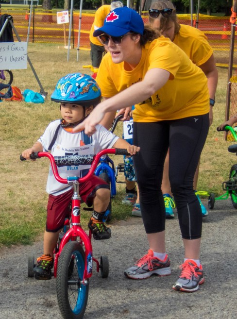 A volunteer helps a toddler with his bicycle at the Shufelt Triathlon in Peterborough Ontario