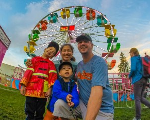 A family poses for a photo in front of a ferris wheel at the Acton Fair in Acton, Ontario