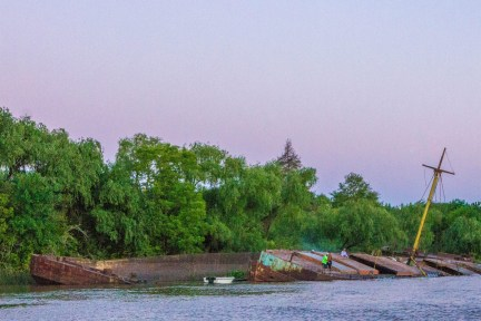 Fishermen cast their lines from a sunken ship on the banks of the delta Parana in Tigre