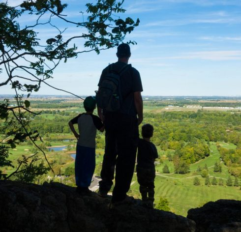 A father and two young boys look out from a cliff at Mount Nemo Conservation Area in Ontario