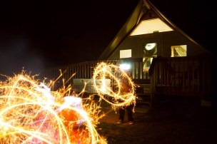 two young boys make sparkler circles in front of a cabin at night in Thousand Islands National Park