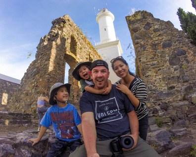 A family of explorers smiles in front of a lighthouse in Colonia, Uruguay