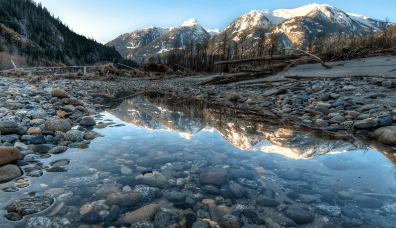 Mountains reflect into a river near Squamish BC on the Sea to Sky Highway one of our Unforgettable Canadian Road Trips