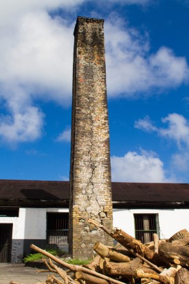 A crumbling stone smoke stack sits against an old spanish style building at the River Antoine Rum Distillery in Grenada