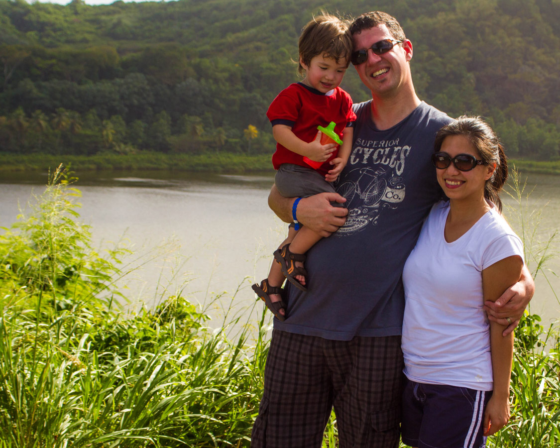 A father, mother and young boy pose for a photo in front of a small lake