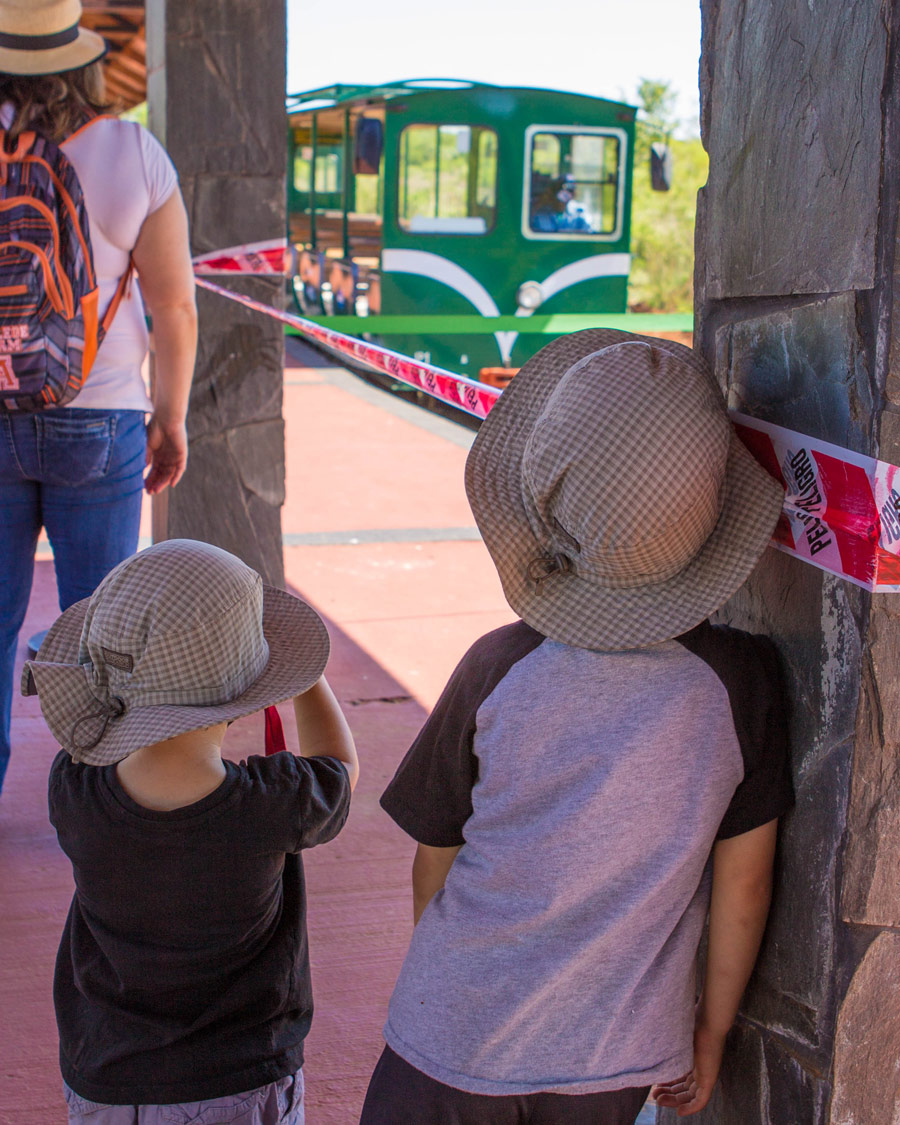 Two boys lean against a post as a small train comes into the station at Iguazu Park Visitor Centre in Argentina