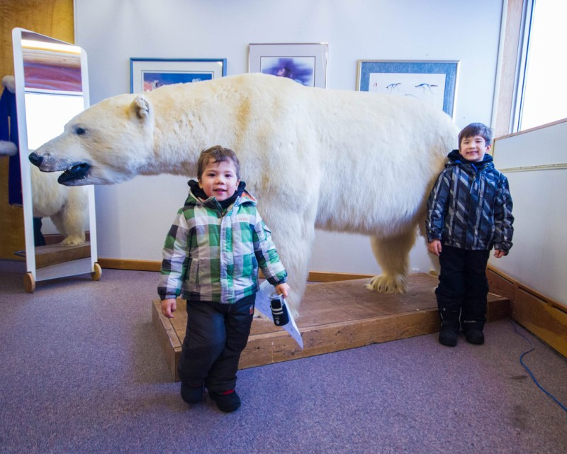 Two young boys pose beside a polar bear at the Northern Frontier Visitor's Center in Yellowknife.