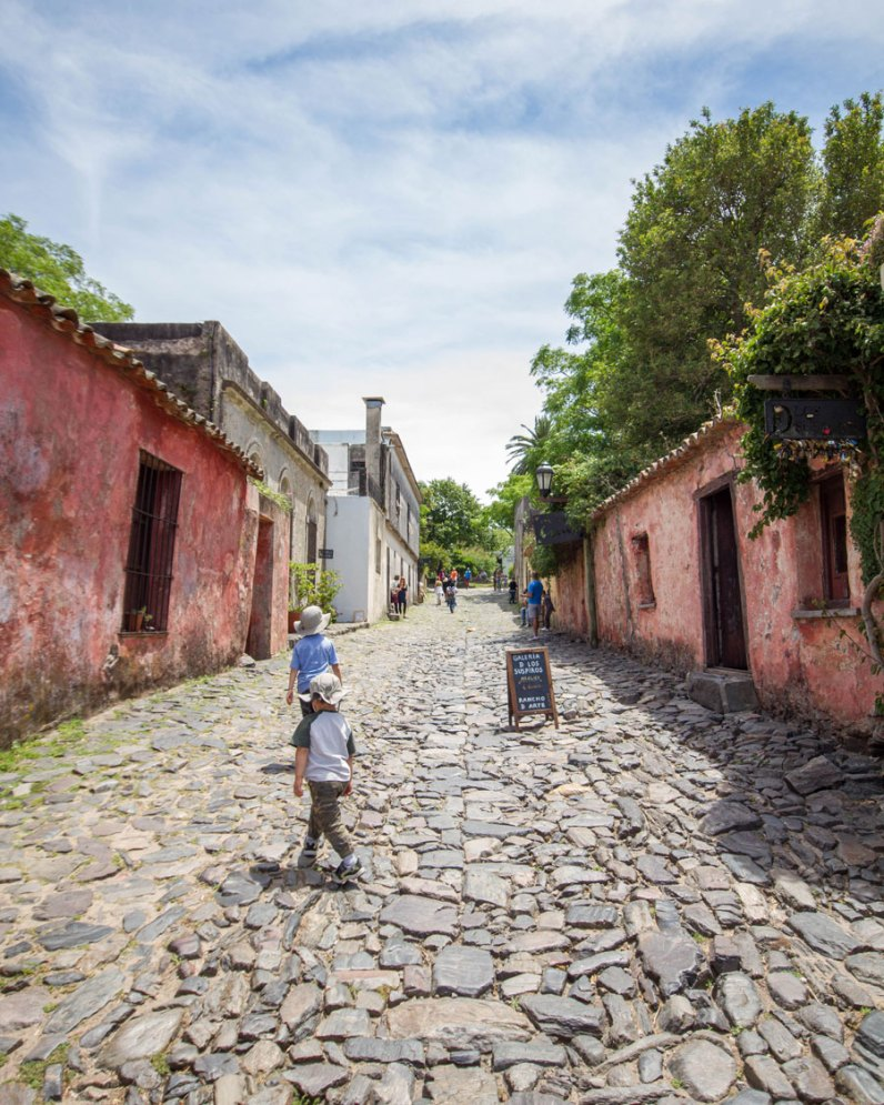 Boys walking the cobblestone street Calle de los suspiros in Colonia del Sacramento, Uruguay.